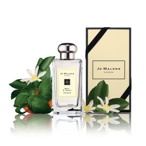 Jo Malone cologne next to packaging and orange.