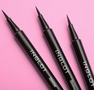 Three eyeliner pens with lids off.