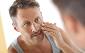 Man touching face looking in mirror.