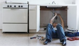 Woman fixing leak under sink.