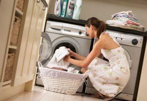 Woman loading laundry machine.