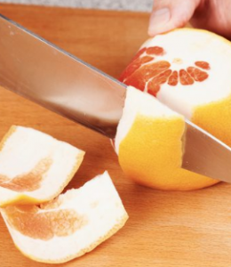 Cutting rind off grapefruit.