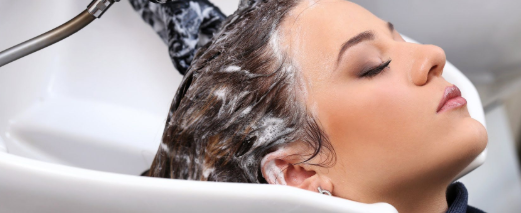Woman getting hair washed at salon.