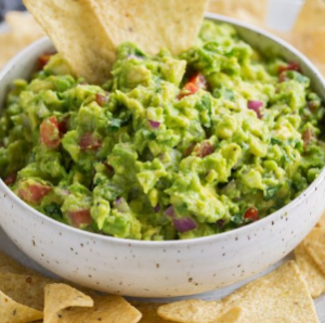 Bowl of guacamole with tortilla chips.