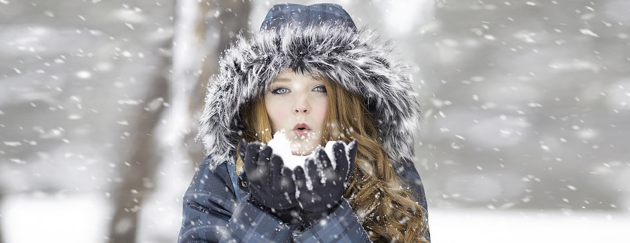 Woman wearing coat with fur hood blowing snow at camera.