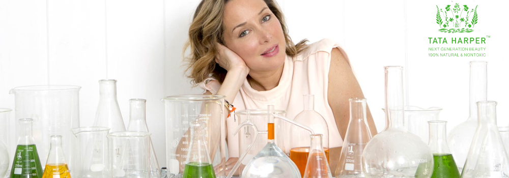 Woman leabing head on her hand with chemistry beakers in front of her.