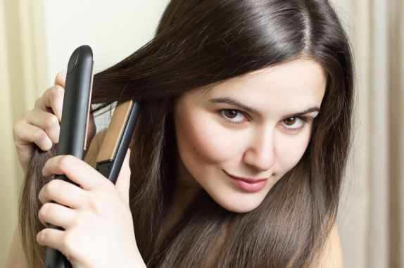 Woman straightening hair with iron.