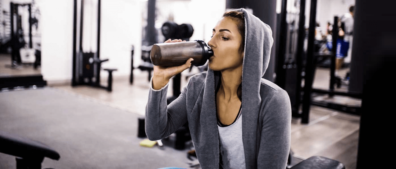 Woman with hoody drinking from bottle.