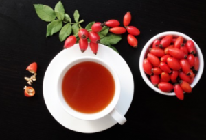 Rose hip tea in teacup with bowl of rose hips next to it.