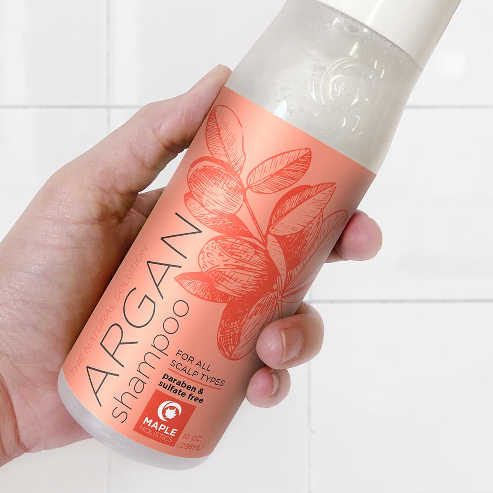 Hand holding a bottle of argan shampoo.