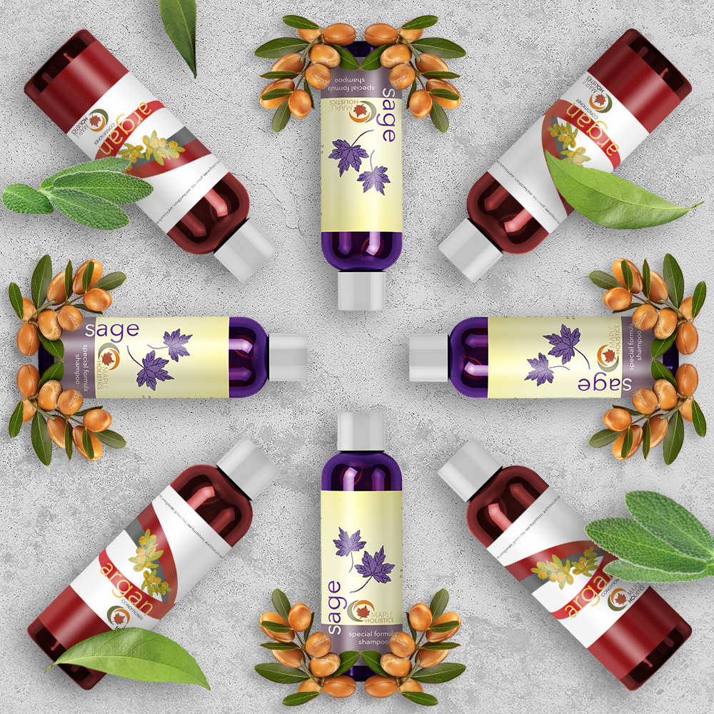 Bottles of sage shampoo and argan conditioner laid out in a circle with leaves and flowers.