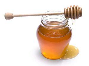 Jar of honey with dipper.