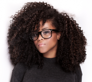 WOman wearing glasses with black kinky-curly hair.