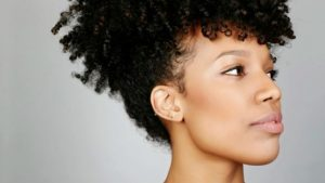 Woman with curly hair pulled back.