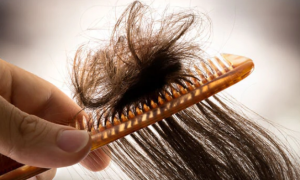 Comb brushing knotted hair.