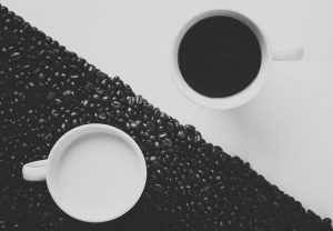 Two mugs with milk and coffee on black and white backgrounds.