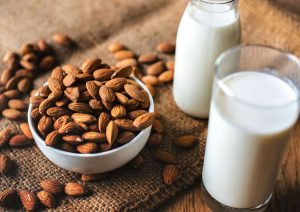Two glasses of almond milk next to bowl of almonds.