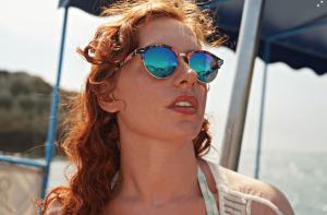 woman with red hair and blue sunglasses.