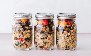 Three jars of quinoa with vegetables.