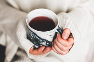 Hands holding mug of red liquid.