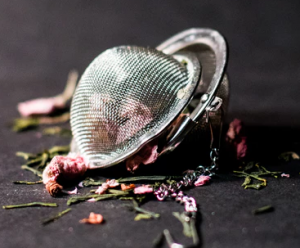 Tea infuser surrounded by herbs.