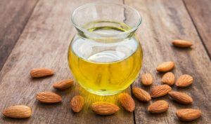 Almond oil and scattered almonds.