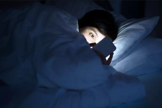 Woman on phone in bed.
