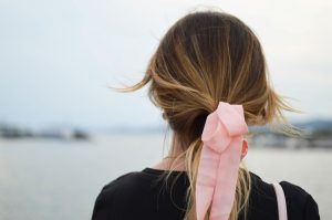 Girl with back to camera and pink bow in hair.
