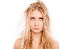 Blonde woman with messy, damaged hair.