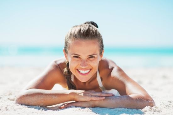 Blonde woman smiling on beach.