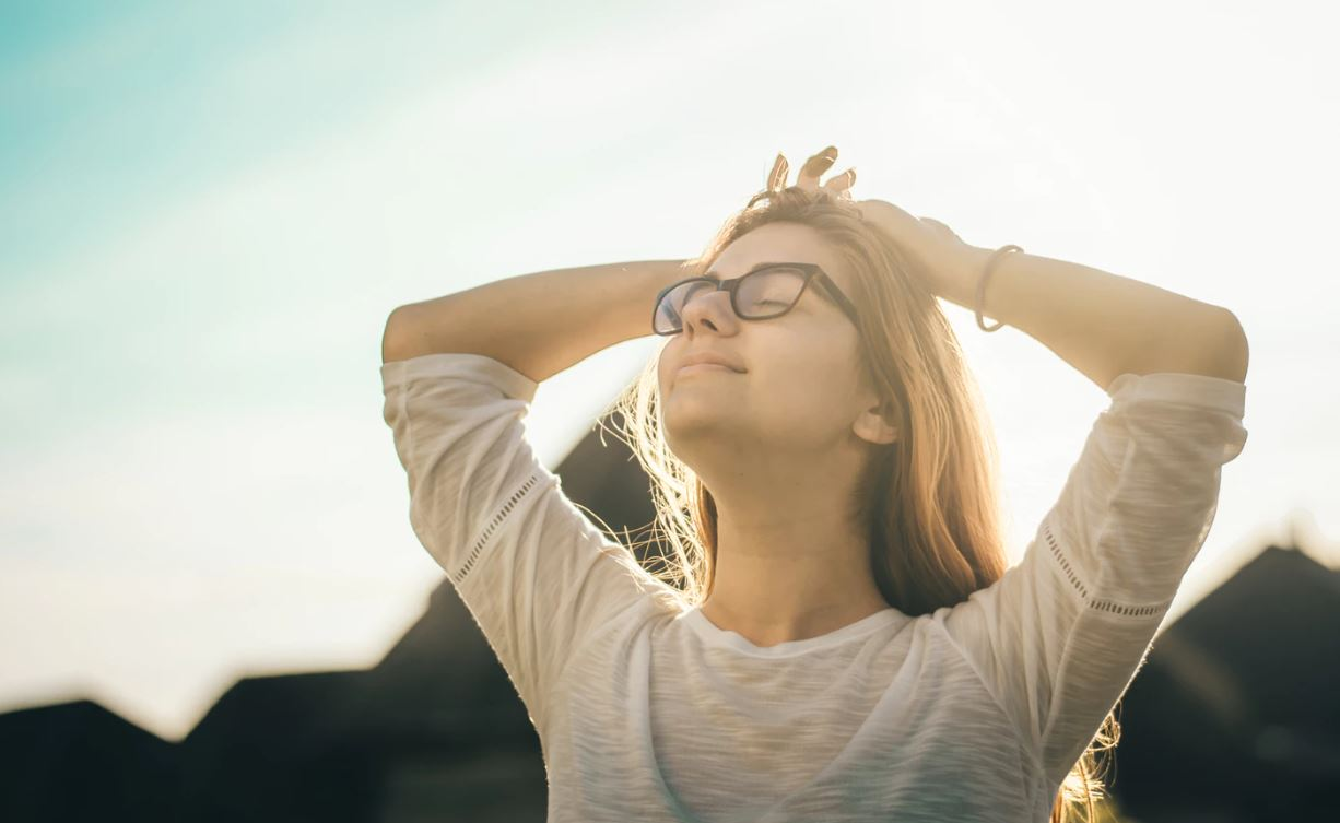 Girl with glasses with hands on head looking peaceful.