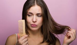 Woman holding comb and her hair.