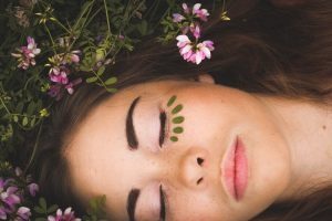 Woman sleeping surrounded by flowers.