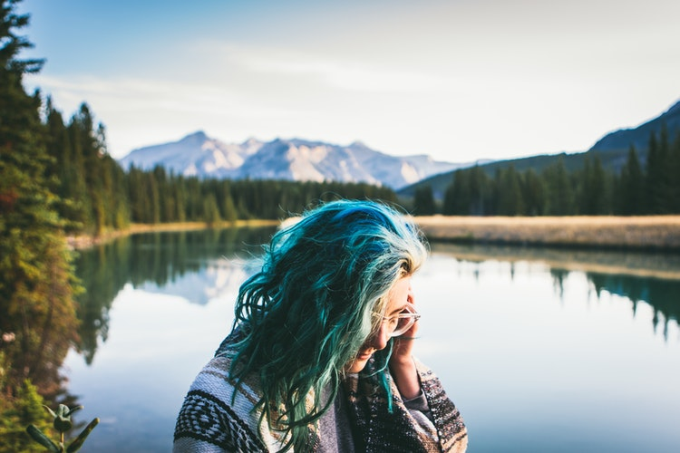 Girl with blue hair in front of lake.