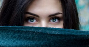 Close up of woman's eyes and lower of half of face covered with scarf.