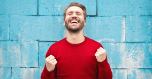 Man smiling with eyes closed and pumping fists.