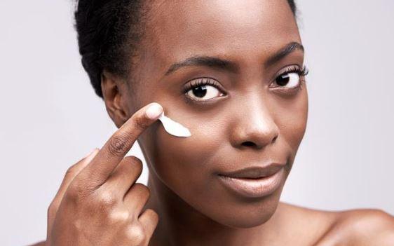Black woman rubbing cream in.