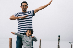 Dad and son raising arms.