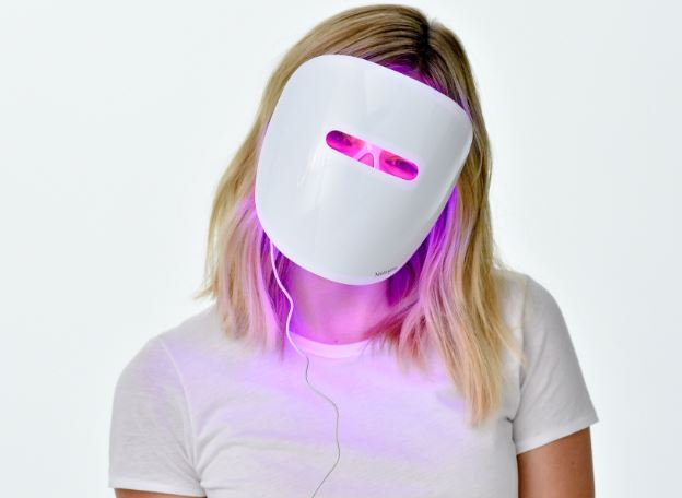 Girl wearing neutrogena light therapy mask for acne.