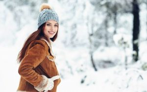 Woman smiling outdoors in winter clothes surrounded by snow.