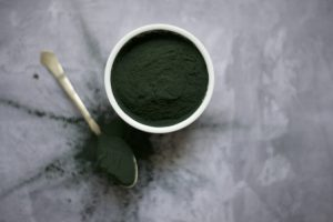 Birds eye view of green powder in pot and on spoon on marble background.