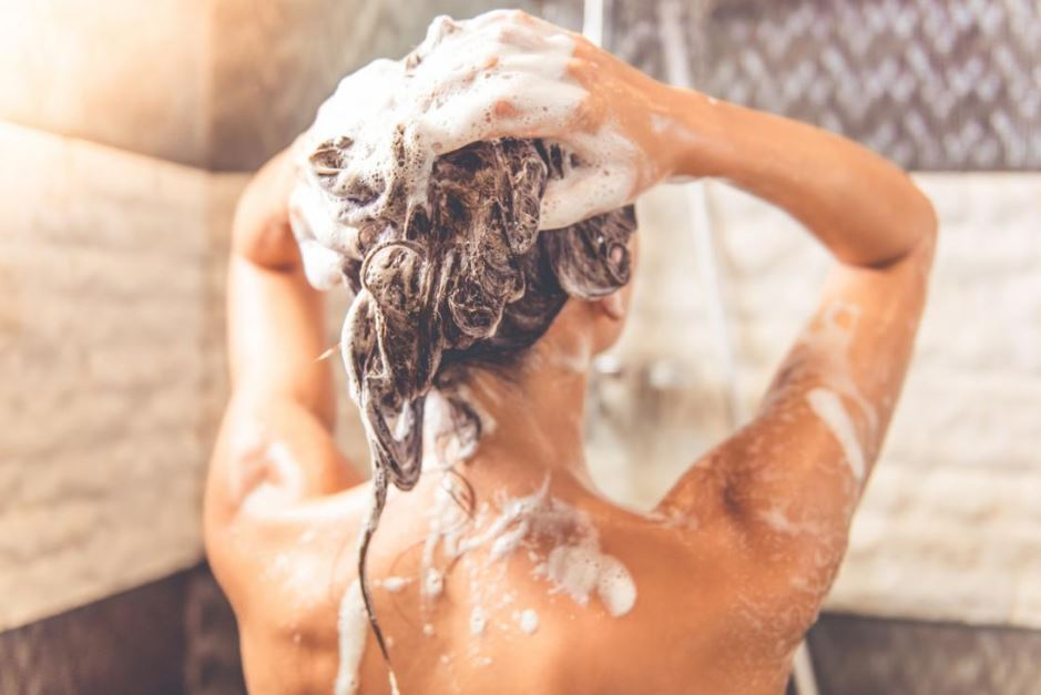 Brunette woman shampooing her hair while showering.