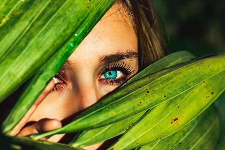 woman looking through leaves.