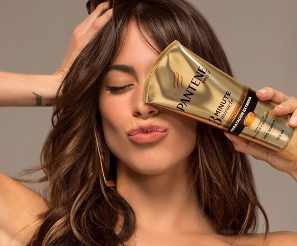 Woman holding a bottle of Pantene 3 Minute Miracle in front of her face.