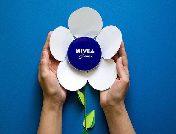 Artistic nivea creme tin over a paper flower.