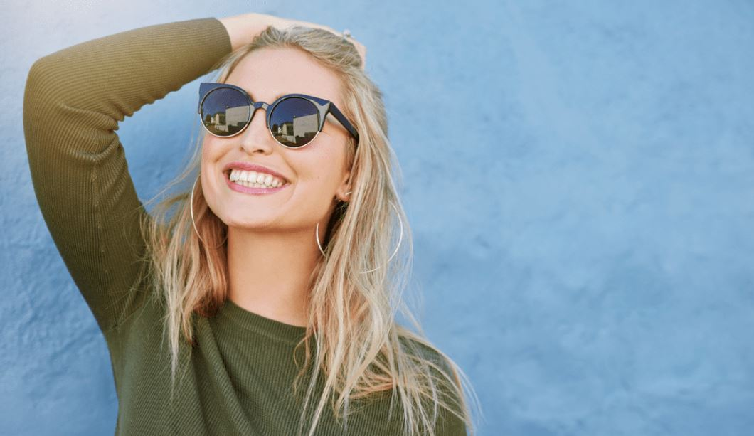 Woman in sunglasses smiling in the sun.
