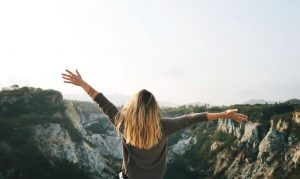 Blonde girl with her arms outstretched in a natural setting.
