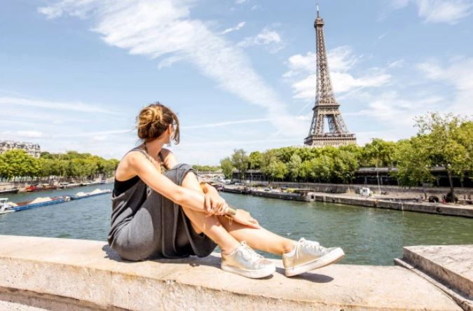 Woman sitting by the eiffel tower.