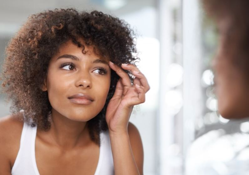 African american woman examining skin in mirror.