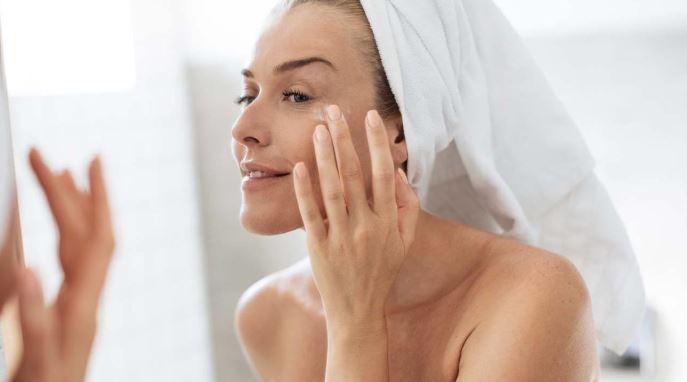 Woman in towel applying eye cream.